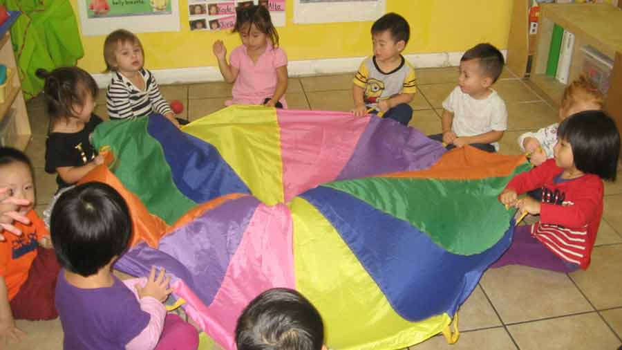 Young students playing with a rainbow-colored parachute